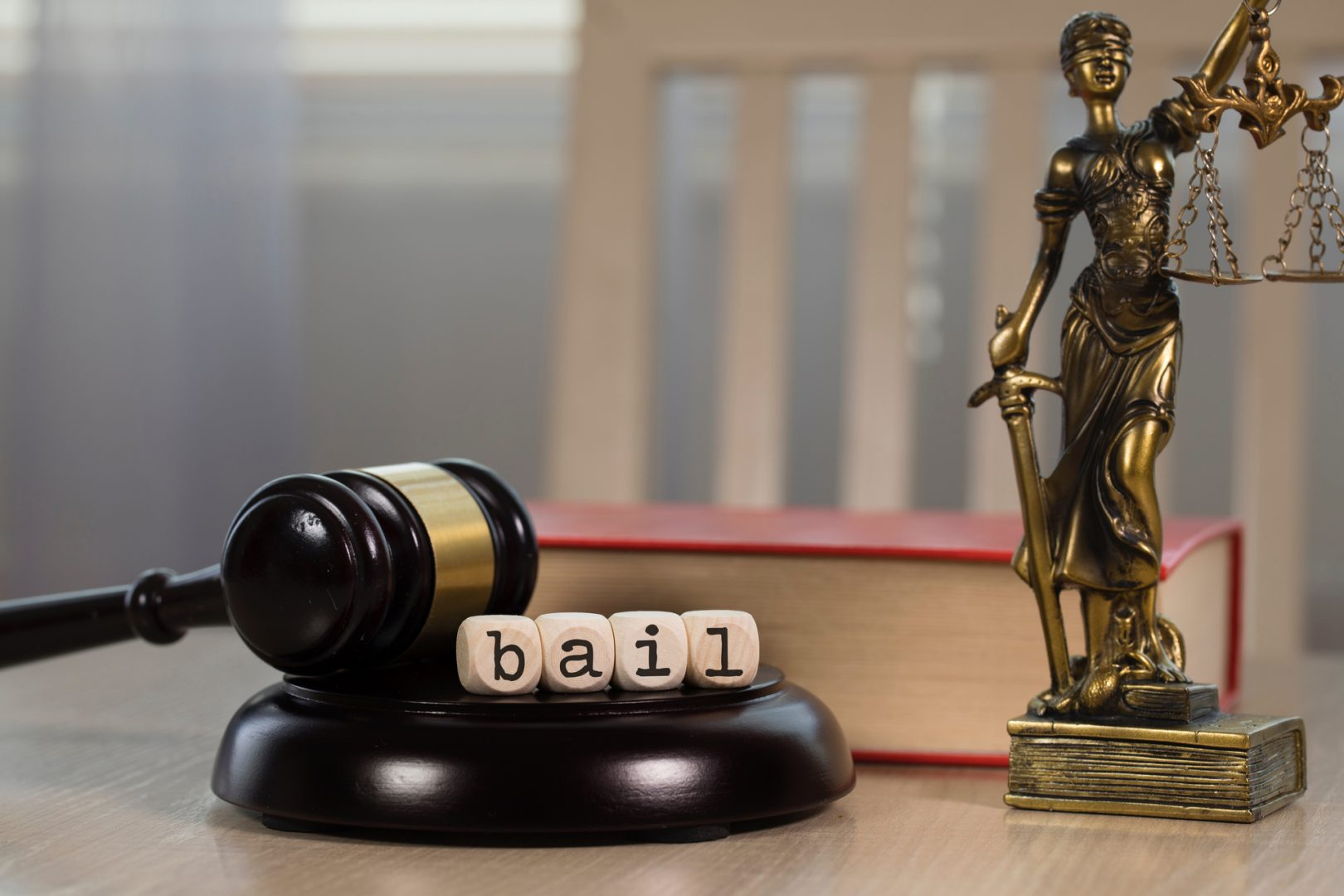 Word BAIL composed of wooden dices. Wooden gavel and statue of Themis in the background.